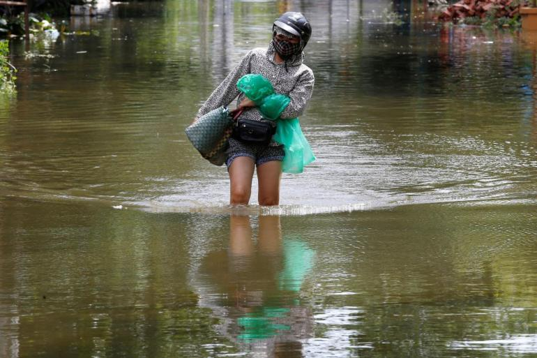 A woman wades through a flooded village after heavy rainfall in Ninh Binh province