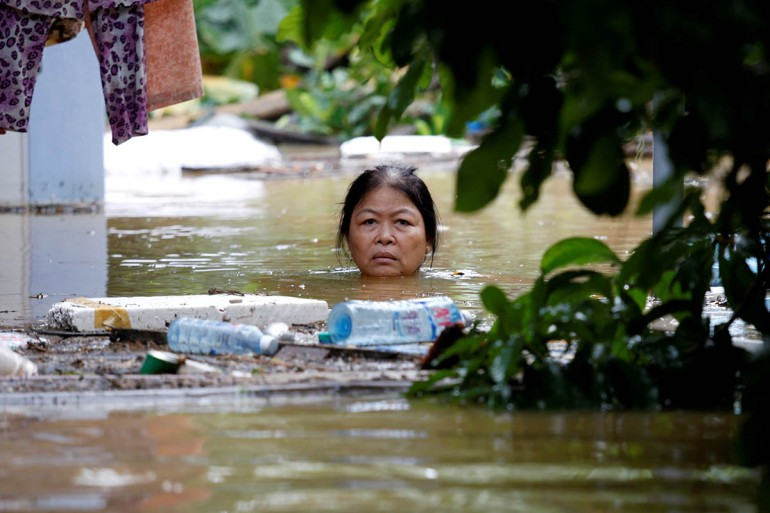A woman wades through a submerged street at the UNESCO heritage ancient town of Hoi An after typhoon Damrey hits Vietnam